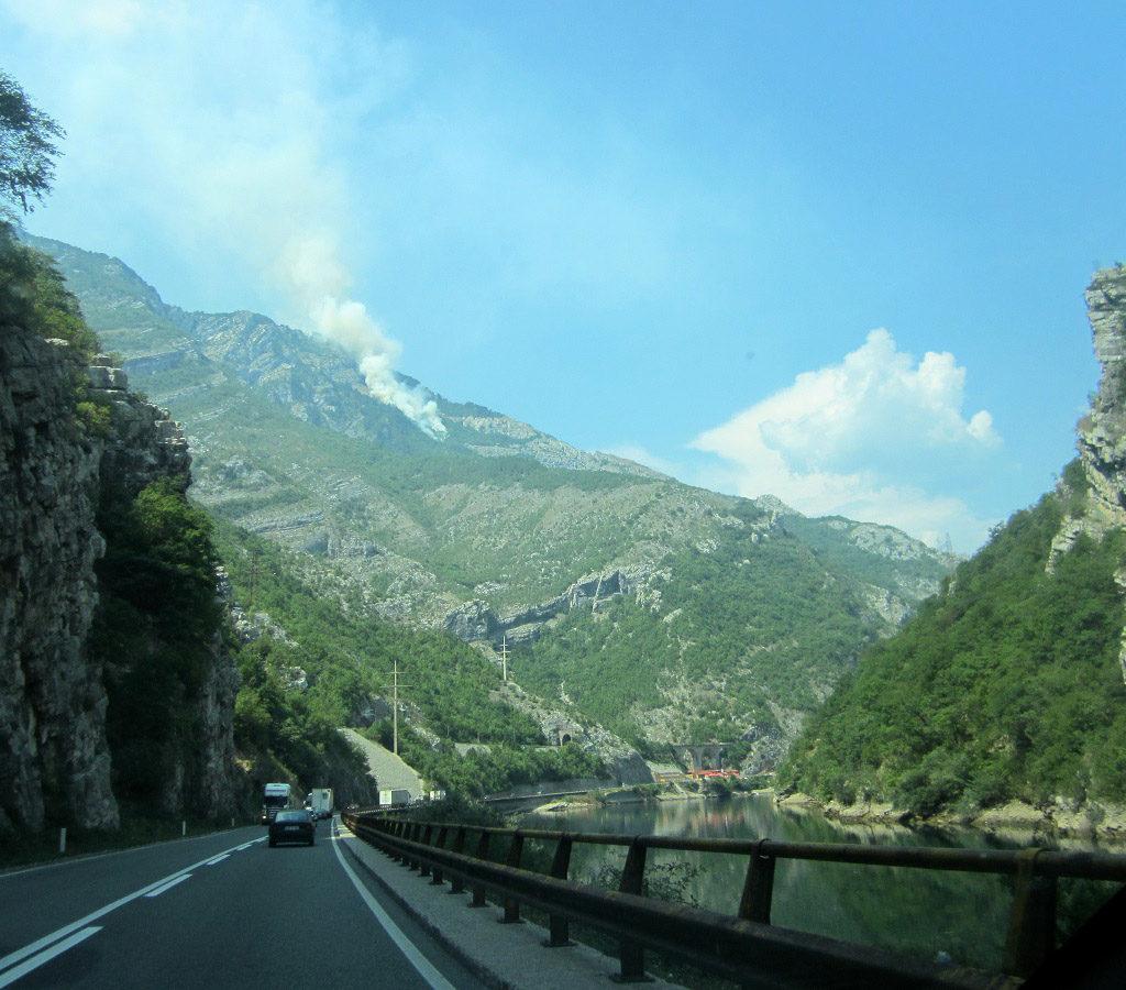 La Carretera, En Buen Estado, Iba Bordeando El Lago. Arriba, En La Montaña, Se Aprecia Un Pequeño Incendio